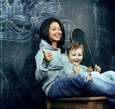 Adolescente joven del inconformista que se sienta con su hermano en sala de clase Imagenes de archivo