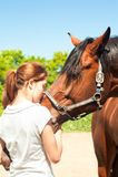 Adolescente joven del pelirrojo que besa su caballo preferido de la castaña Imagen de archivo libre de regalías
