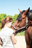 Adolescente joven del pelirrojo que besa su caballo preferido de la castaña Foto de archivo libre de regalías