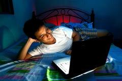 Adolescente joven delante de un ordenador portátil y en una cama Imagen de archivo