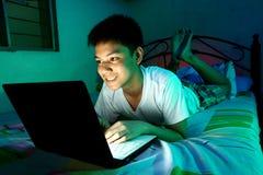 Adolescente joven delante de un ordenador portátil y en una cama Fotos de archivo libres de regalías