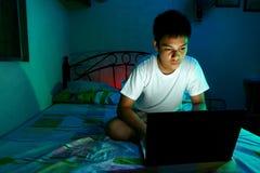 Adolescente joven delante de un ordenador portátil y en una cama Imágenes de archivo libres de regalías