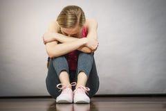 Adolescente joven deprimido triste que se sienta por la pared Imagenes de archivo