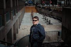 adolescente joven diseñado en las gafas de sol que se oponen a fondo céntrico del parque del cuadrado de ciudad Foto de archivo