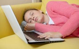 Adolescente joven dormido con el ordenador portátil imagenes de archivo