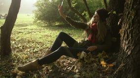 Adolescente joven elegante alegre que toma las fotos del uno mismo por el teléfono en parque del otoño metrajes