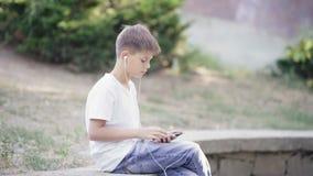 Adolescente joven en auriculares con el smartphone que se sienta en la música que escucha del encintado almacen de metraje de vídeo