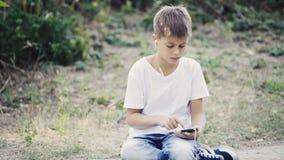 Adolescente joven en auriculares con el smartphone que se sienta en la música que escucha del encintado almacen de video