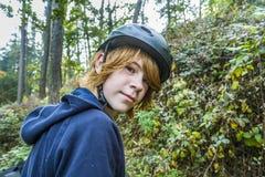 Adolescente joven en bosque con el casco de la bici Fotos de archivo