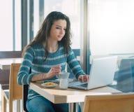 Adolescente joven en el café que practica surf la red Foto de archivo libre de regalías