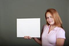 Adolescente joven en el estudio con una muestra en blanco Foto de archivo libre de regalías