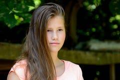 Adolescente joven en el parque con la expresión facial tranquila Fotos de archivo