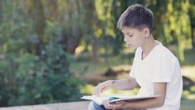 Adolescente joven en el parque que se sienta en el encintado y que escribe su preparación almacen de metraje de vídeo
