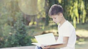 Adolescente joven en el parque que se sienta en el libro del encintado y de lectura almacen de video