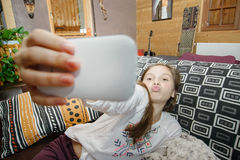 Adolescente joven en el sofá casero del sofá que toma el selfie Foto de archivo libre de regalías