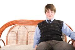 Adolescente joven en el sofá de mimbre Imágenes de archivo libres de regalías