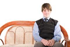 Adolescente joven en el sofá de mimbre Foto de archivo