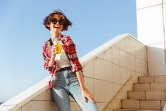 Adolescente joven en gafas de sol que bebe el zumo de naranja Imagen de archivo