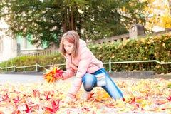 Adolescente joven en hojas de la cosecha del parque del otoño Temporada de otoño Foto de archivo libre de regalías