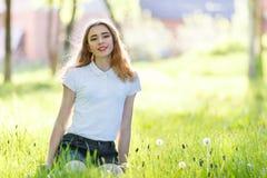 Adolescente joven en la camisa blanca que se sienta en hierba Fotografía de archivo