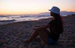 Adolescente joven en la playa en la puesta del sol Imágenes de archivo libres de regalías