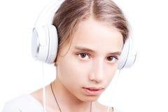 Adolescente joven en las auriculares aisladas en blanco Imágenes de archivo libres de regalías