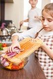 Adolescente joven en verduras de ensalada de mezcla del delantal Fotos de archivo libres de regalías