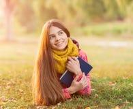 Adolescente joven feliz con el libro en el parque del otoño Imagen de archivo
