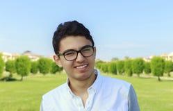 Adolescente joven feliz con ojo-desgaste en el jardín Imagenes de archivo