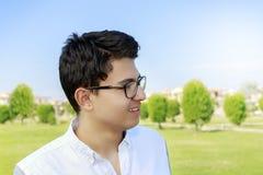 Adolescente joven feliz con ojo-desgaste en jardín Fotografía de archivo
