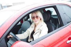Adolescente joven feliz en su nuevo coche rojo Foto de archivo