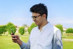 Adolescente joven feliz que mira en teléfono elegante Foto de archivo