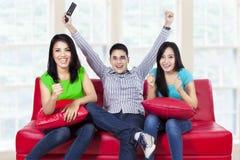 Adolescente joven feliz que ve la TV en casa Imagenes de archivo