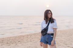 Adolescente joven femenino hermoso asiático que se relaja en la playa detrás Fotografía de archivo