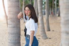 Adolescente joven femenino hermoso asiático que se relaja en la playa detrás Foto de archivo libre de regalías