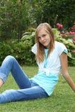 Adolescente joven fino que se relaja en el césped Imagen de archivo libre de regalías