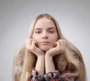 Adolescente joven hermoso con el pelo rubio bastante largo aislado en el fondo blanco Fotos de archivo