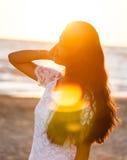 Adolescente joven hermoso con un vestido blanco en la playa en los soles Fotos de archivo libres de regalías