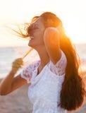 Adolescente joven hermoso con un vestido blanco en la playa en los soles Fotografía de archivo libre de regalías