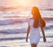 Adolescente joven hermoso con un vestido blanco en la playa en los soles Foto de archivo