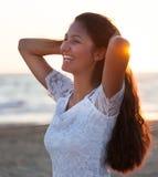 Adolescente joven hermoso con un vestido blanco en la playa en los soles Imagenes de archivo