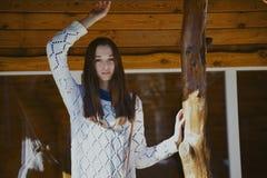 Adolescente joven hermoso que presenta cerca de un edificio de madera en el ci Imagenes de archivo