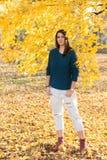 Adolescente joven hermoso que presenta debajo de árbol con las hojas amarillas en el parque en el otoño Fotos de archivo libres de regalías