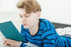 Adolescente joven hermoso que se relaja con un libro Imagenes de archivo
