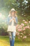 Adolescente joven hermoso que sostiene las flores en rayos de la luz del sol Fotos de archivo