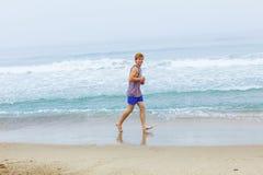 Adolescente joven lindo joging en la playa vacía Foto de archivo