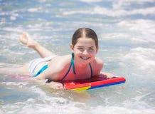 Adolescente joven lindo que sonríe mientras que en un tablero del carretón Fotografía de archivo