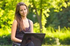 Adolescente joven lindo usando latop al aire libre. Fotos de archivo