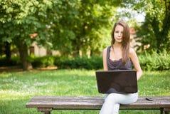 Adolescente joven lindo usando latop al aire libre. Fotografía de archivo libre de regalías