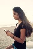 Adolescente joven mientras que usa el smartphone en la playa Imágenes de archivo libres de regalías